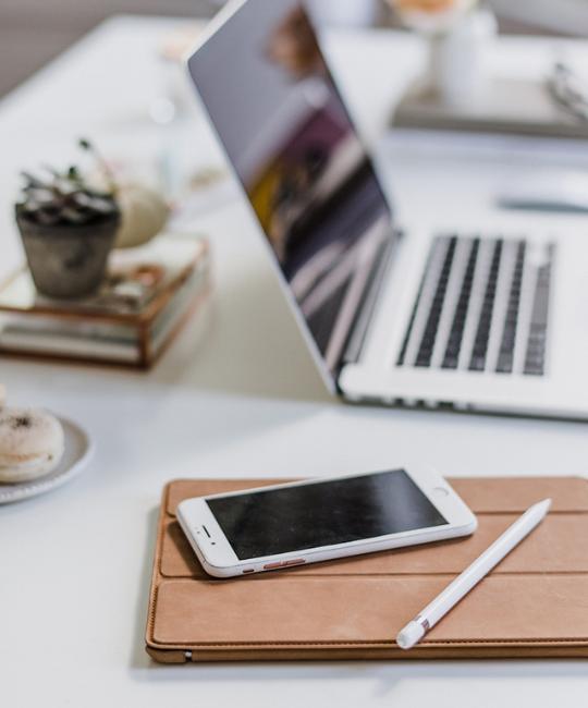 Ausschnitt eines Arbeitsplatzes mit Laptop und Smartphone