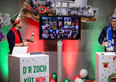 Zwei Männer stehen am Rednerpult. Um sie herum ist bunt dekoriert, in der Mitte steht ein Monitor mit Liveübertragung, Videokonferenz