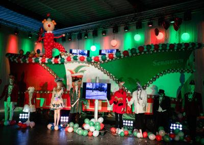 Karnevalistisch dekorierte Halle, in der Halle steht ein Karnevalszug, in der Mitte steht ein Montor