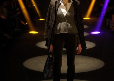 Model auf Laufsteg trägt dunkle Herbstkleidung und eine schwarze Tasche