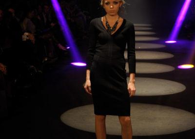 Model auf Laufsteg trägt schwarzes Kleid