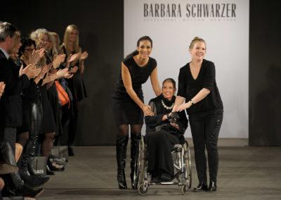 Die Designerin der Modenschau sitzt im Rollstuhl auf dem Laufsteg und wird bejubelt