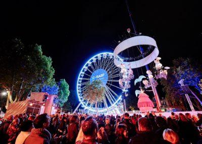 Riesenrad mit BASF Fernerkennung, Bäume werden angestrahlt, viele Gäste sind zu Besuch und schauen sich die Highlights des Events an