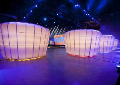 Beleuchtete Booths / Messestände bestehend aus Podest, Tragwerk, Stoffe, Türgrafik, Beleuchtung, Elektrik, Im Hintergrund ist Bühne zu sehen, davor stehen Stühle