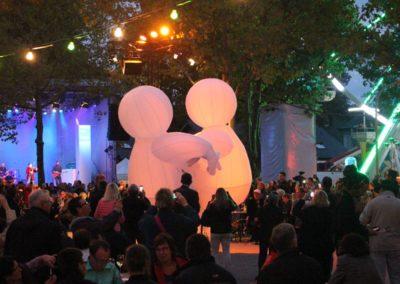 Aufblasbare mit Helium gefüllte Ballonfiguren, bunte Lichterketen hängen in den Bäumen, auf der Bühne spielt eine Band, Zuschauer sitzen auf Bänken im Publikum