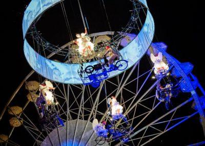 Artisten scheweben mit einem Dreirad in der Luft