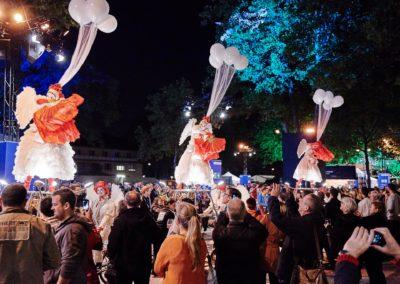 Artisten mit pompösen Kleidern haben mit Helium gefüllte Luftballons an ihren Hüten und stehen auf Podesten und tanzen, Zuschauer sehen zu