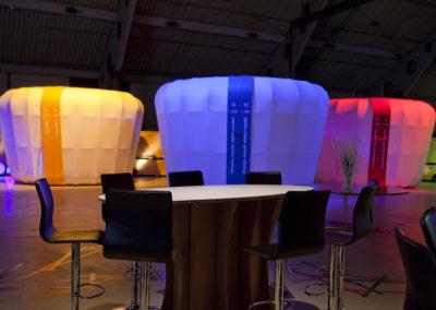 Beleuchtete Booths / Messestände bestehend aus Podest, Tragwerk, Stoffe, Türgrafik, Beleuchtung, Elektrik, Stehtisch aus Karton