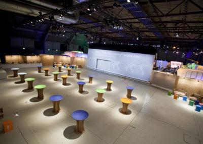 Beleuchtete Booths abgetrennt von Messewänden aus Holz, Stehtische aus Karton, Loungemöbel aus Karton