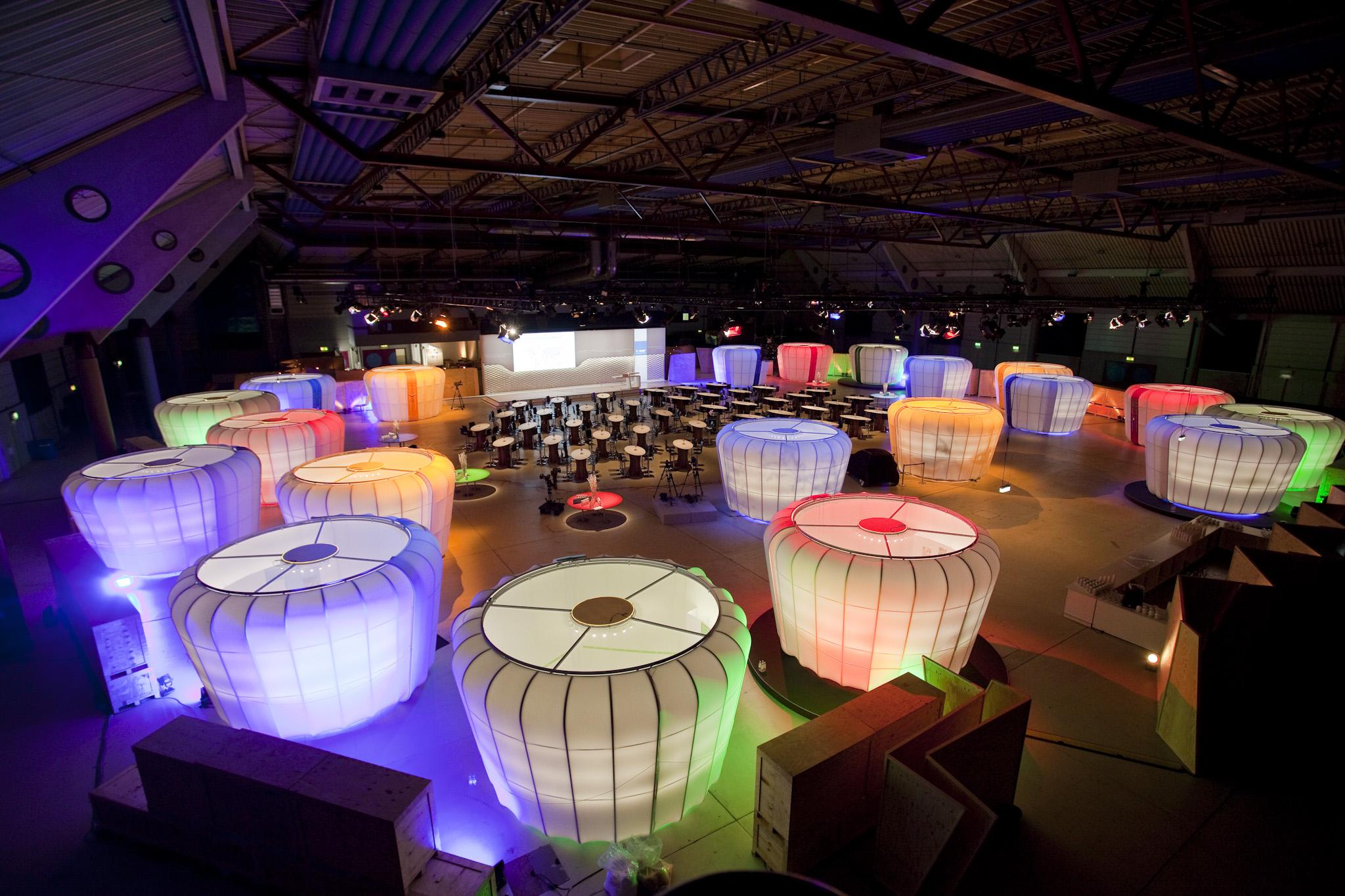 Beleuchtete Booths abgetrennt von Messewänden aus Holz, nachhaltige Stehtische, Bühne mit Messerückwand