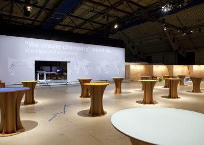 Große bedruckte Bühnenrückwand mit Weltkarte, Vor der Bühne stehen Stehtische aus Karton mit bunter Tischplatte, Bereich ist abgetrennt durch Messewände aus Holz
