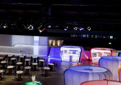 Vogelperspektive Beleuchtete Booths / Messestände bestehend aus Podest, Tragwerk, Stoffe, Türgrafik, Beleuchtung, Elektrik, Stehtisch aus Karton, Bühne