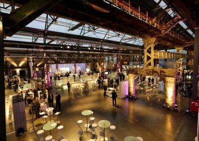 Industriehalle, offen gestaltete Messestände mit Counter, Stehtischen und Barhockern, Sitzmöglichkeiten an weißen Brückentischen mit Barhockern