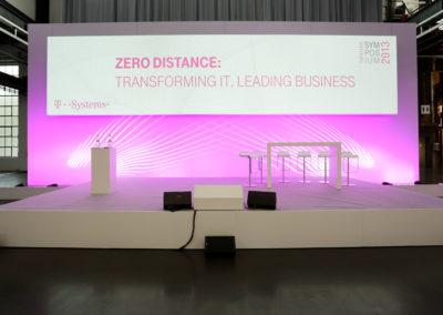 Bühne mit Bühnenrückwand aus Print Frame Alurahmen, auf der Bühne steht ein Brückentischen mit weißen Barhockern