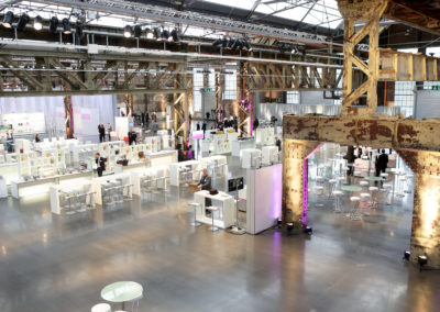 Bühne mit Fadenvorhang von Buffet getrennt, Catering / Loungebereich mit weißen Brückentischen und weißen Barhockern