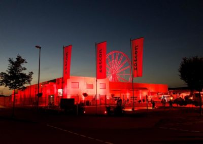 Beleuchtetes Firmengebäude, Scheinwerfer rot, Beleuchtetes Riesenrad