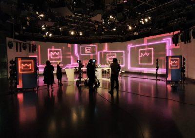 Fernsehstudio, mit Moderationstisch, Kameras und Monitoren, Traversen mit Scheinwerfern an der Decke, Beleuchtete Aluspannrahmen als Rückwand