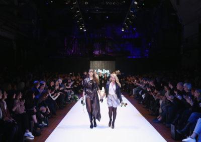 Models laufen hintereinander in einer Reihe über den Laufsteg
