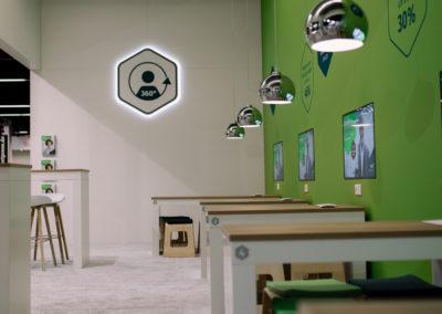 Alu-Messebausystem aus 4-Kantprofilen. An Messerückwand hängen Monitore. Weiße Tische mit Holzplatte, Pendelleuchten hängen über den Tischen