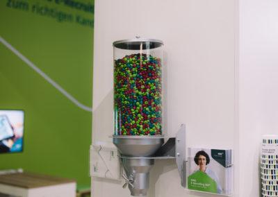 Süßigkeitenmaschine an Messewand, daneben Prospekthalter