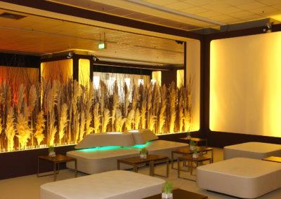 Loungemöbel mit Lehne aus Holzunterkonstruktion mit Kunstleder bezogen, Lehne in organischer Form mit Beleuchtung, Tische Nussbaum, Pampasgras als Abtrennung und Sichtschutz