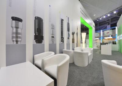 Loungebereich mit weißen Sesseln und weißen Couchtischen, Messewand mit Posterbeklebung, Grauer Teppichboden