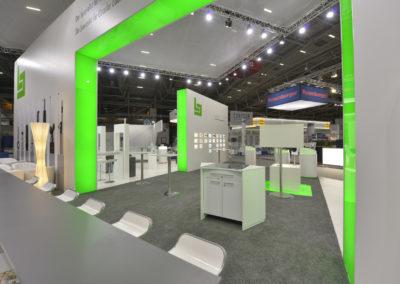 Hebeboden mit grauem Teppich, konventionelle Bauelemente aus KS Spanplatte, runde und beleuchtete Präsentationsstelen, Messewand mit integrierten Präsentationsfenstern