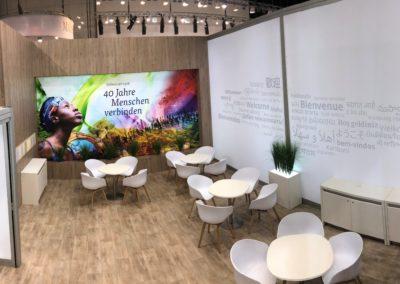 Quadro Wandbau, Holzoptik mit Textilhalteprofilen, Wandfläche größtenteils hinterleuchtet, Loungebereich Stuhl Hay weiß Eiche mit Tisch Inox weiß, Schließfachschrank, Sideboard