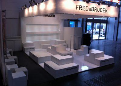 Bodenmodule in weißer Backsteinoptik dienen als Präsentationsfläche der Taschen, Deckenrahmen, Traversenverkleidung, Cube Loungemöbel, Hebeboden