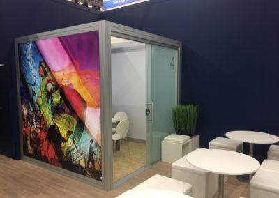 Quadro Vierkantprofile mit Glas Schiebetüren, Beiger Teppichboden, LED Posterboxleiste für Quadro Rahmen, PVC Bodenbelag, weiße Würfelhocker mit Beistelltisch Inox
