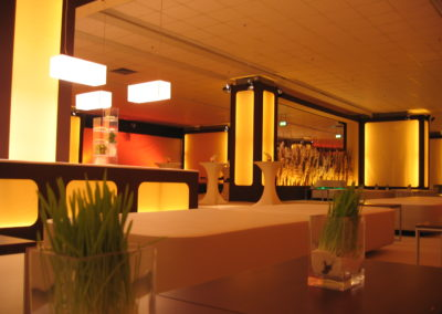 Loungemöbel weiß mit Beistelltischen aus Nussbaum, Stehtische mit weißen Hussen überzogen, Pampasgras als Raumtrenner und von unten beleuchtet