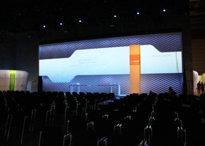Vogelperspektive, man sieht Bühne mit großer beleuchteter Bühnenrückwand, in der Mitte Bestuhlung, außen herum beleuchtete Booths / Messestände