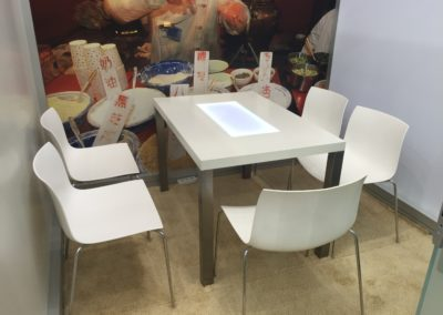 Quadro Vierkantprofile mit Glas Schiebetüren, Beiger Teppichboden, LED Posterboxleiste für Quadro Rahmen, Tisch Inox mit glatt-glänzender Oberfläche, weiße Konferenzstühle