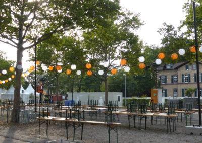 Bierzeltgarnituren, Lampions-Lichterketten hängen zwischen den Bäumen