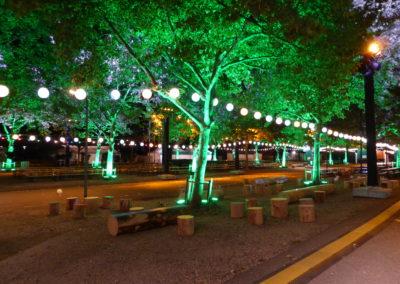 Inszeniertes Baummaterial, Baumsitzlandschaft, Sitzhocker Baumstamm, Sitzbank Baumstamm, Lampion Schirme, Outdoorlampen, Lichterketten hängen zwischen den Bäumen