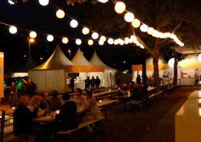 Pagodenzelte stehen zwischen Bäumen, in den Bäumen hängen Lichterketten, Auf Bierzeltgarnituren sitzen Gäste