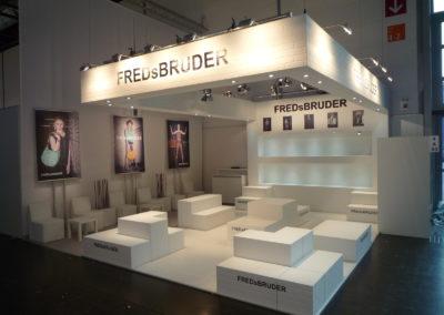 Bodenmodule in weißer Backsteinoptik dienen als Präsentationsfläche der Taschen, Deckenrahmen, Traversenverkleidung, Cube Loungemöbel, Roll-up