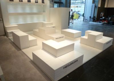 Bodenmodule in weißer Backsteinoptik dienen als Präsentationsfläche der Taschen, Deckenrahmen, Traversenverkleidung, Backsteinwand mit beleuchteter Einbuchtung
