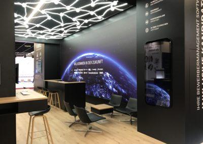 Messestand mit Systemboden, Wandbau Grafik, hinterleuchteter Digitaldruck, LED Wand-Cluster, Säulentische, Loungemöbel, Sternenhimmel, Fangnetz LED-Schläuche, Theke