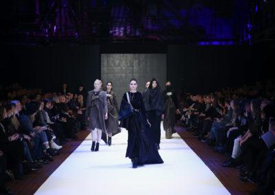Models laufen über den Laufsteg. Links und rechts sitzt Publikum