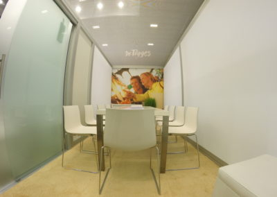 weißer langer Konferenztisch mit weißen Stühlen, beiger Teppich, Grafik in Aluspannrahmen an der Wand