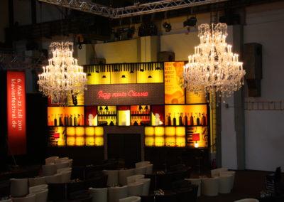 Cocktailbar gelb beleuchtet, Kronleuchter hängen von der Decle, Loungemöbel weiß
