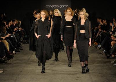 Schwarz angekleidete Models laufen hintereinander über den Laufsteg, links und rechts sitzen Zuschauer