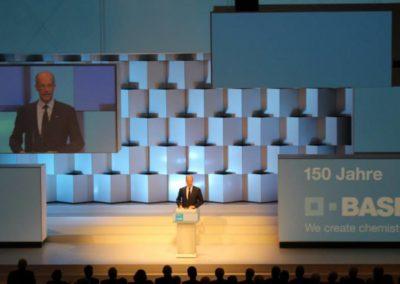 Mann steht auf der Bühne und hält eine Rede am Rednerpult. Bühnenrückwand aus Kuben, Monitor hängt von der Decke