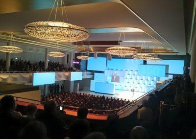 Festsaal, Politiker hält Rede auf der Bühne, Große Lampen hängen von der Decke