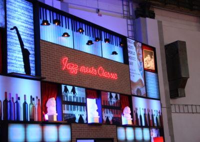 Beleuchtete Bühnenkulisse, Backstein, Jazz, Wein, Bar, Schriftzug Lampe