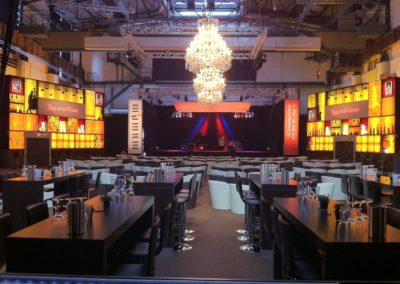 Cocktailbar gelb beleuchtet, Kronleuchter hängen von der Decle, Loungemöbel weiß, Bühne mit Schlagzeug
