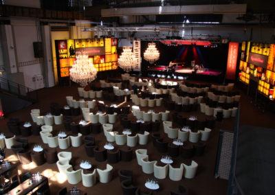 Bühne mit Klavierspieler, Kronleuchter hängen von der Decke, Loungesessel mit Tisch für Zuschauer, links und rechts beleuchtete Bühnenkulisse Bar