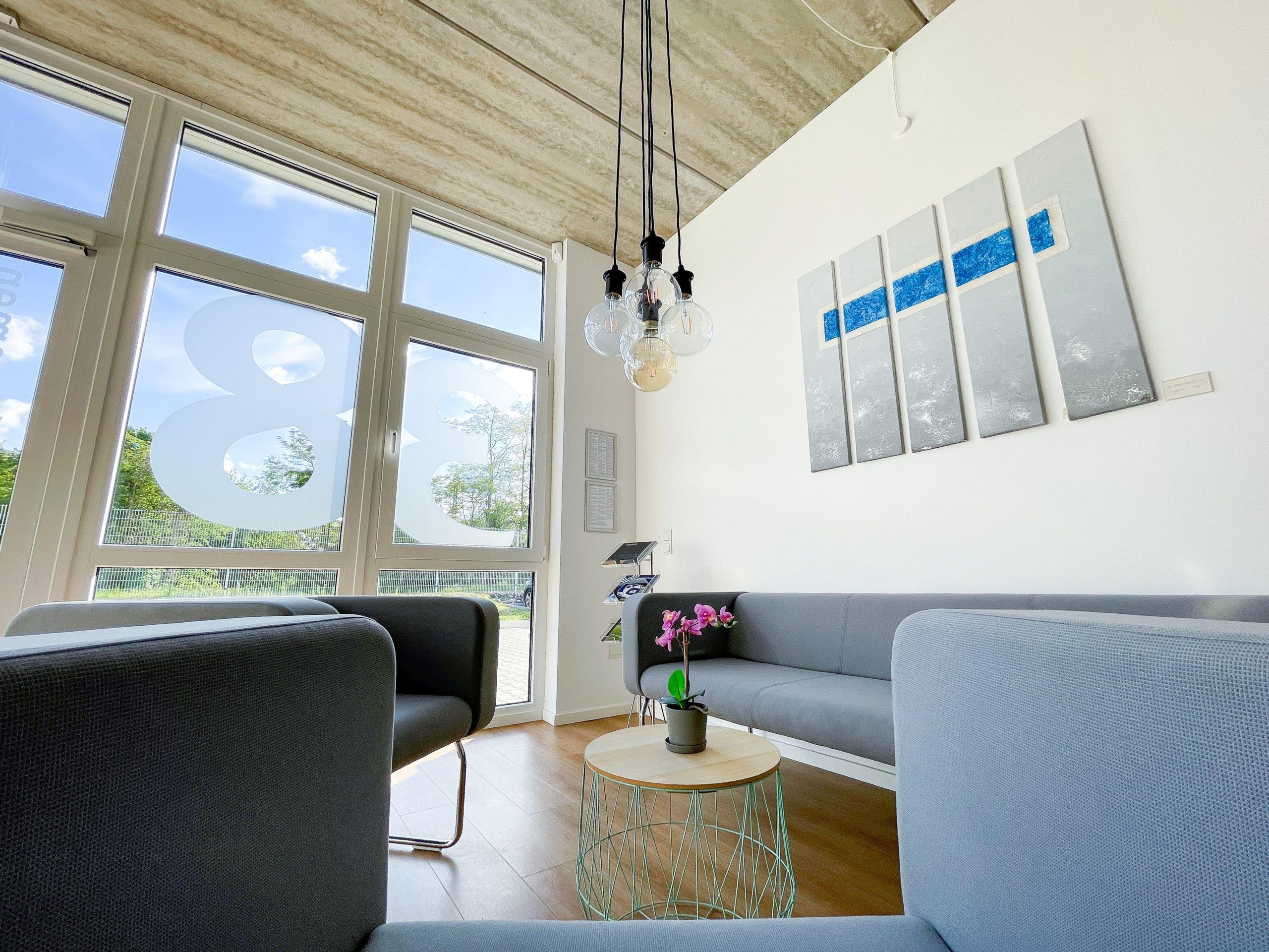 Setcon Empfangsbereich mit grauem Sofa und zwei Sesseln, Pendelleuchten hängen von der Decke