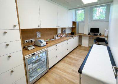 Laborraum, Behandlungsliege, mehrere Einbau- und Hängeschränke, Medizinkühlschrank, ein Computer und medizinische Geräte
